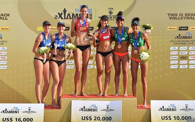Beach volleyball players stand atop the medal stand in Xiamen