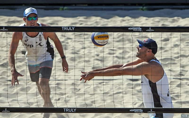 Beach volleyball player Phil Dalhausser sets the ball for partner Nick Lucena