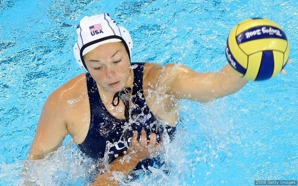 Criag #12 of the United States looks to move the ball against Liu Ping #3 of China during their preliminary round water polo match